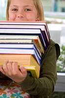 Girl 7-9 with pile of books, portrait