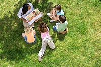 Teacher reading book to children 5-9 outdoors, elevated view