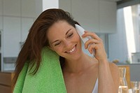 Woman drying her hair and phoning