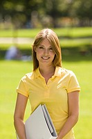 Portrait of young woman holding folder outdoors