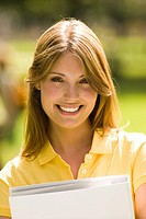 Portrait of young woman holding folder outdoors (thumbnail)