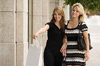 Young women shopping together and woman pointing