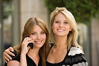 Happy portrait of young women while on cell phone