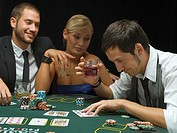 People with drinks playing poker game
