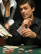 Man at poker game with woman holding cash