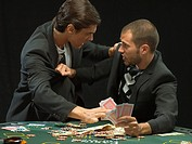 Men fighting at poker game