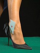 Detail of woman's foot with playing card
