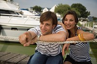 Young couple sitting on pier with man pointing
