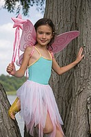 Young girl with fairy wings and wand standing in tree (thumbnail)