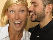 Man whispering in woman's ear (thumbnail)