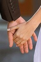 Detail of bride and groom holding hands