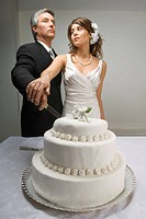 Serious bride and groom cutting wedding cake