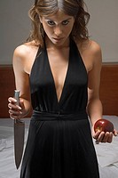 Intense woman holding knife and apple