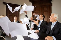 Happy businesspeople throwing papers in the air