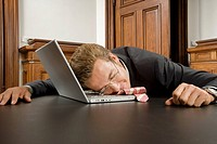 Businessman asleep with laptop