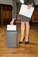 Businesswoman shredding papers