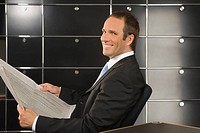 Portrait of a businessman holding a financial newspaper and smiling in an office