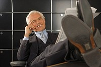 Portrait of a businessman holding a newspaper in an office and smiling (thumbnail)