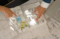 High angle view of a man and a woman's hands pointing at an architectural model