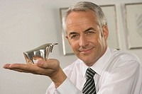 Portrait of a businessman holding a bull figurine and smiling