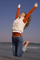 Woman in winter clothing jumping in the air at the beach