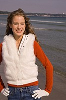 Young woman in winter clothing at the beach
