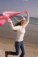 Young woman in winter clothing running with scarf in air at the beach