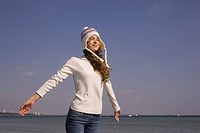 Young woman in winter clothing feeling the breeze at the beach