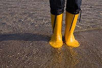 Detail of yellow boots standing in water at the beach