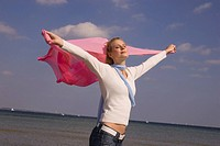 Young woman holding pink scarf in the breeze at the beach with eyes closed