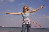 Happy young woman at beach with hula hoop