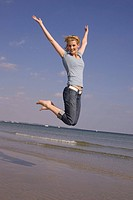 Happy young woman jumping in the air at the beach