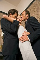 Side profile of two men kissing a young woman