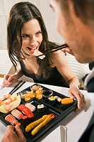 Close-up of a man feeding a sushi with chopsticks to a woman in a restaurant