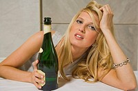 Portrait of a young woman holding a champagne bottle and leaning on a dining table