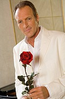 Portrait of a mature man holding a Rose and smiling