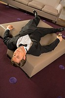 High angle view of a young man lying on an ottoman and holding a champagne flute