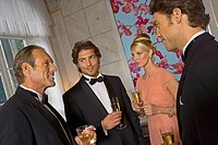 Four people holding champagne flutes and talking to each other