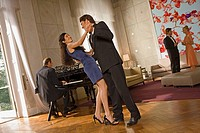 Side profile of a young couple dancing with a mature man playing a piano