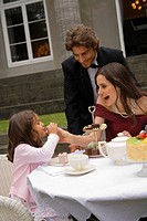 Young woman feeding cake to her daughter with a young man standing behind her