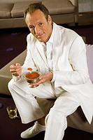 Portrait of a mature man sitting on a stool and eating caviar with a spoon