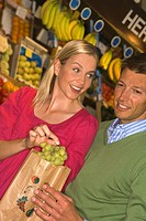 Mid adult couple buying fruits from a supermarket and smiling