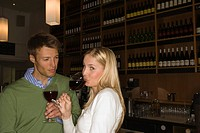 Side profile of a mid adult woman drinking wine with a mid adult man looking at her