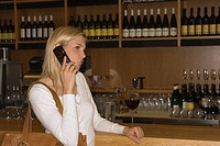 Woman standing at a bar counter and talking on a mobile phone