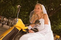 Portrait of a bride riding a motor scooter and smiling