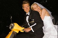 Portrait of a newlywed couple on a motor scooter and smiling
