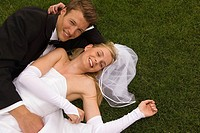 Portrait of a newlywed couple lying on grass and smiling