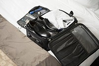 Businessman's packed suitcase on bed (thumbnail)