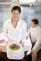 Waitress holding plate of food