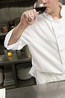 Male chef drinking glass of wine